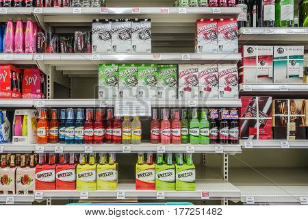 BANGKOK, THAILAND - FEBRUARY 10, 2017 : Shelves with bottles low alcohol drinks selling of Spy, Breezer in Tesco lotus supermarket. Tesco is the world's second largest retailer