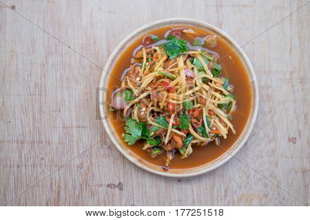 Spicy cockle salad on wooden background. Thai food