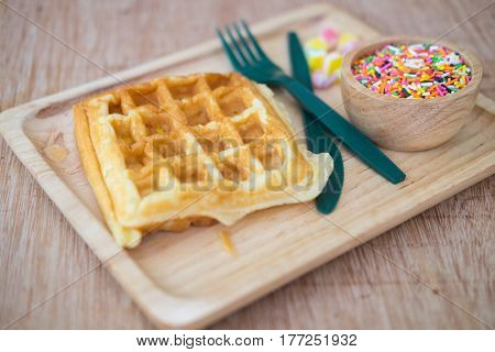 Waffle with topped fruit jelly candy and sugar sprinkle dots on wood tray