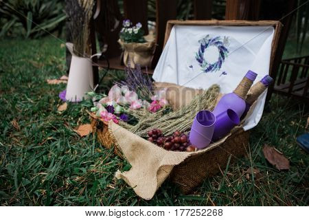Basket with flower and lavender Glass and bottle in grass