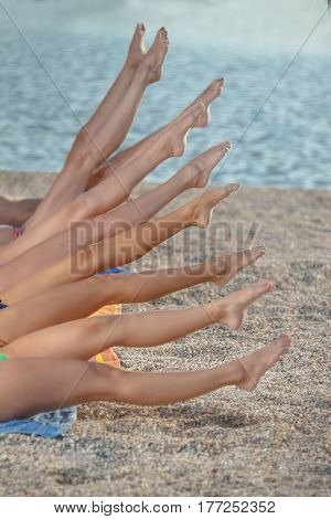 Legs of several girls lying on sandy beach and tanning in the bright summer sun