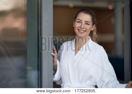 Woman In Bathrobe Opening Glass Door