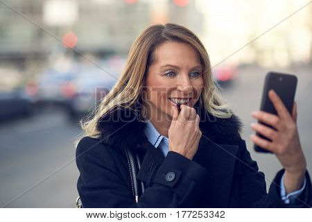Smiling Woman Looking Into Her Phone On Street