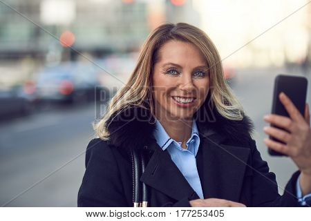 Smiling Woman Holding Her Phone On Street