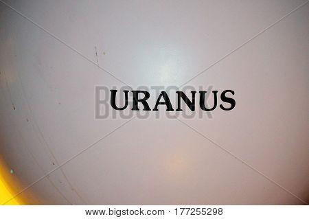 horizontal shot of labeled Uranus planet all capital letters