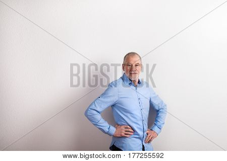 Handsome senior man in light blue shirt smiling, arms on hips. Studio shot against white wall.