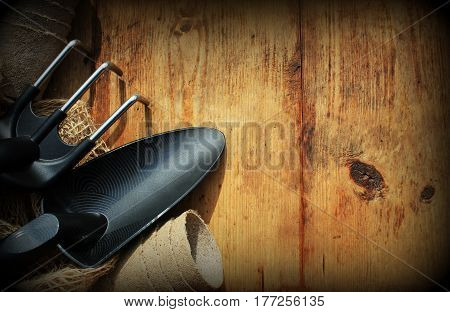 Gardening concept background with garden tools and pots on wooden background. Top view.