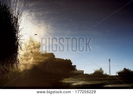 Abstract landscape. Morning mist on water highlighted by rising sun. Shore is reflected in river at dawn