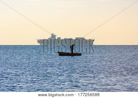 Man and ship. Silhouette of fisher in boat in sea in early morning. Seascape at dawn