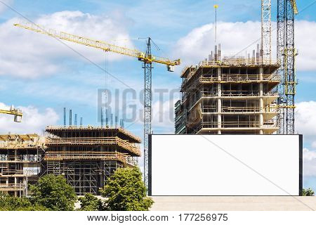 Construction site with cranes and empty advertising billboard in foreground