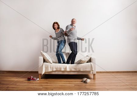 Beautiful senior couple in love standing on couch, dancing, having fun. Studio shot against white wall.