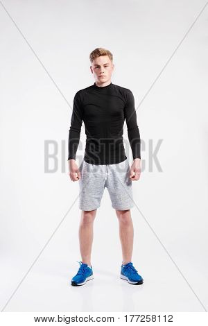 Handsome hipster fitness man in black t-shirt and gray shorts. Studio shot on gray background.