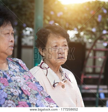 Candid shot of Asian mature women chatting at outdoor park in the morning.