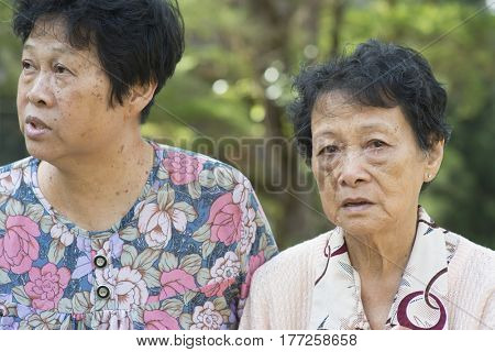 Candid shot of Asian elderly women gossip at outdoor park in the morning.