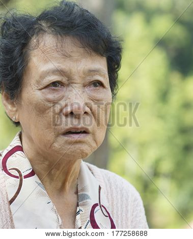 Portrait of worried Asian senior adult woman at outdoor garden park in the morning.