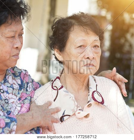 Candid shot of Asian elderly women chit chatting at outdoor park in the morning.
