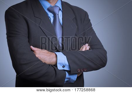 business man in a stylish suit standing with folded arms.
