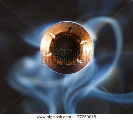 Copper colored hollow point and smoke pointed at the camera