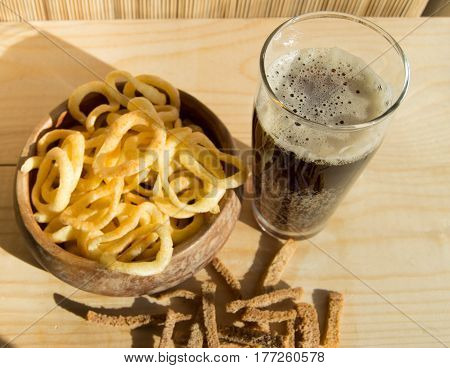 Plate of chips, glass of dark beer with foam, bubbles and crackers on wooden background.
