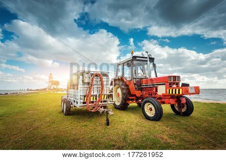 Red Tractor With Trailer On The Grass Field