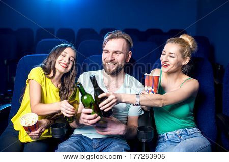 Happy friends clinking bottles sitting in the cinema