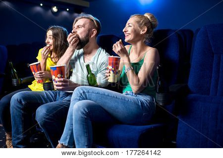 Happy friends watching film sitting together with popcorn in the cinema