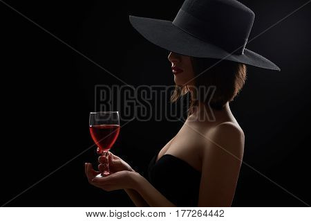 Wine time Studio shot of a mysterious woman in a black dress and a hat hiding her face holding a glass of red wine on black background lighting shadows mystery incognito winery dark elegance concept.