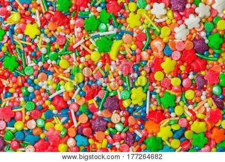 Sweet sugar spreading pastry decoration. Сlose view of colorful candy sprinkles.