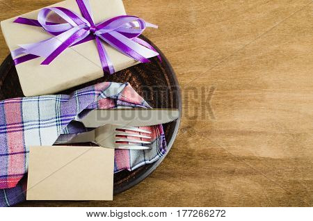 Festive Table Setting. Cutlery with Empty Tag and Present on Linen Napkin on Rustic Wooden Background. Father's Day Concept. Copy Space. Selective Focus.