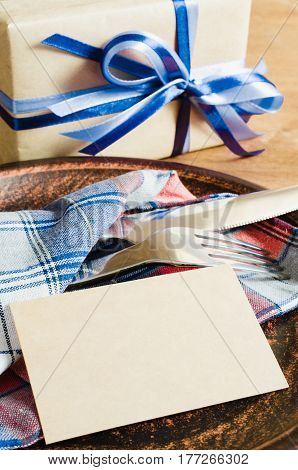 Dining Table Setting. Cutlery with Empty Tag and Present on Linen Napkin on Rustic Wooden Background. Father's Day Concept. Copy Space. Selective Focus.