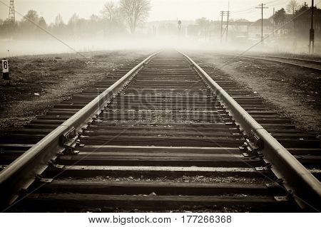Railroad track disappearing in fog with some distant houses and telephone poles along the way