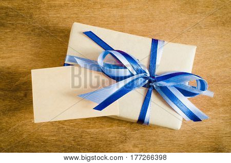 Present with Empty Tag on Rustic Wooden Background. Concept Father's Day or Birthday. Copy Space. Selective Focus.