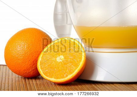Still life with oranges and a juice extractor closeup