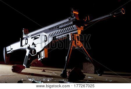 Semi automatic black rifle with orange light from the side on a dark background