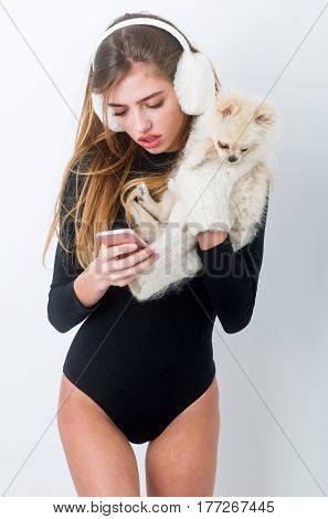 Pretty Girl In Earmuffs Holding Pomeranian Dog And Using Smartphone