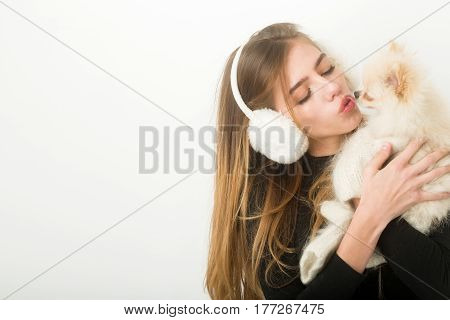 Sexy Pretty Girl Kissing Small Pomeranian Dog In Earmuffs