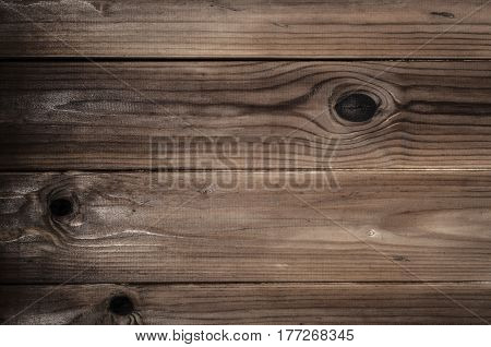 Background texture of heavily knotted faded and weathered old wood planks. Midtone brown.