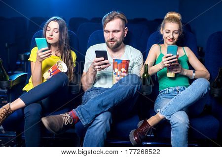 Young friends using smart phones sitting together in the cinema