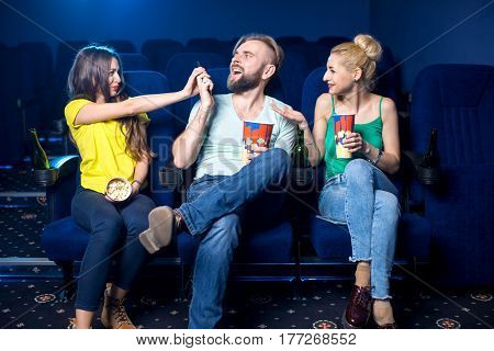 Rude man talking with phone sitting with women in the cinema