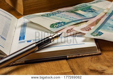 On the wooden surface is an open diary a few bills and a fountain pen