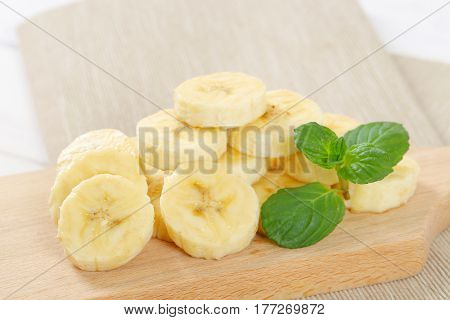pile of sliced banana on wooden cutting board - close up