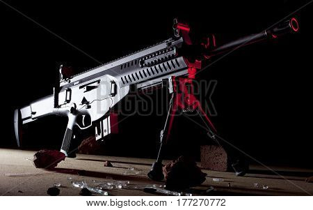 Black rifle with red side lighting on a dark background