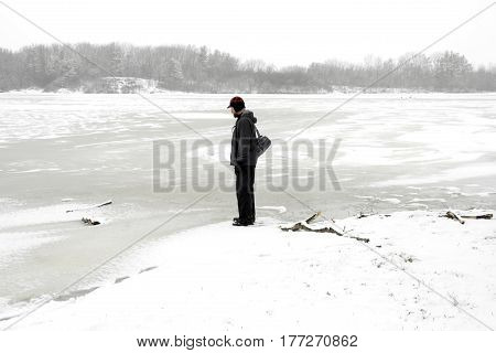 Rugged outdoors man stopping to look at a frozen lake while on a winter hike