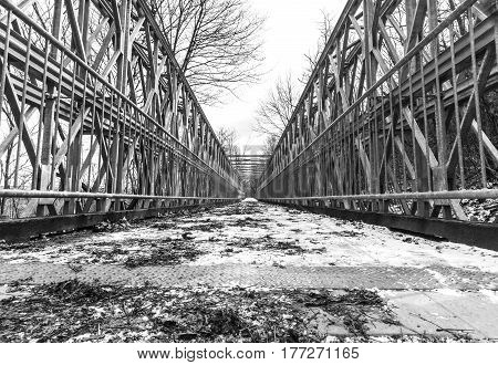 Symmetrical metal bridge with footpath from low perspective with wide angle high contrast balance in black and white