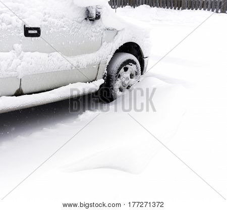 White truck parked in driveway covered with deep snow during winter storm