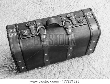 Top view of vintage leather suitcase in black and white standing up on bed travel concept