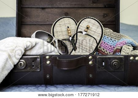 Vintage suitcase open and packed with beach items travel concept