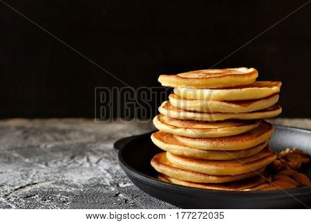 Hot fresh Pancake in a cast iron skillet with nuts on a stone