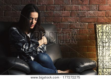 Depressed young woman on brick wall background