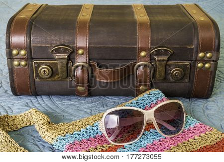 Vintage suitcase sunglasses and woven colorful purse on bed packed and ready for travel
